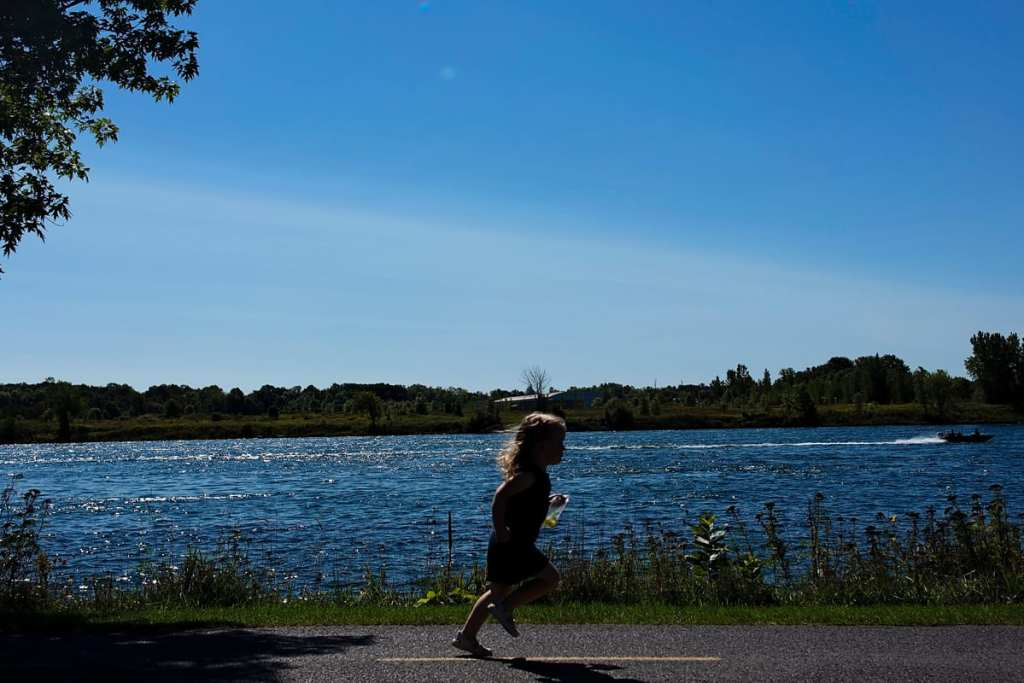 little girl running down path beside St Lawrence River