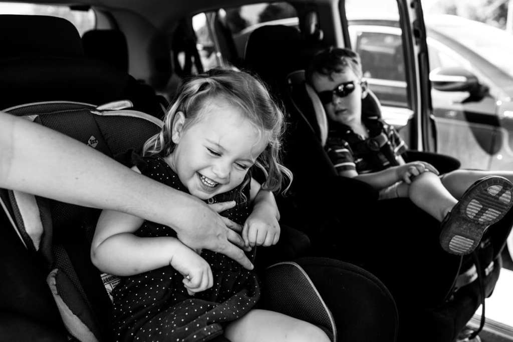 Brother and sister laughing and being tickled in backseat