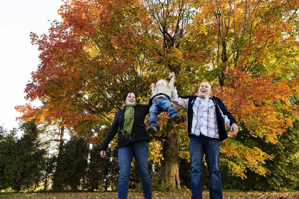 mom and dad swinging little boy in rural fall photo shoot