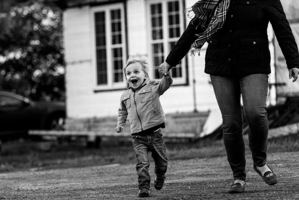 young boy running and laughing holding mom's hand in rural family shoot