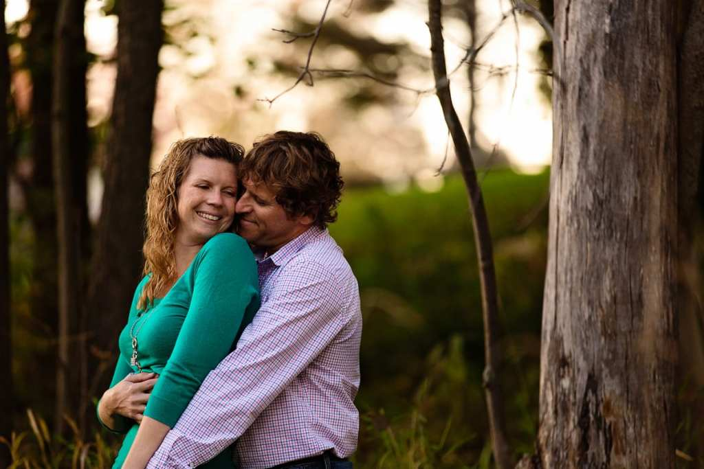 Smiling woman in bright green sweater and fiance in fall engagement session