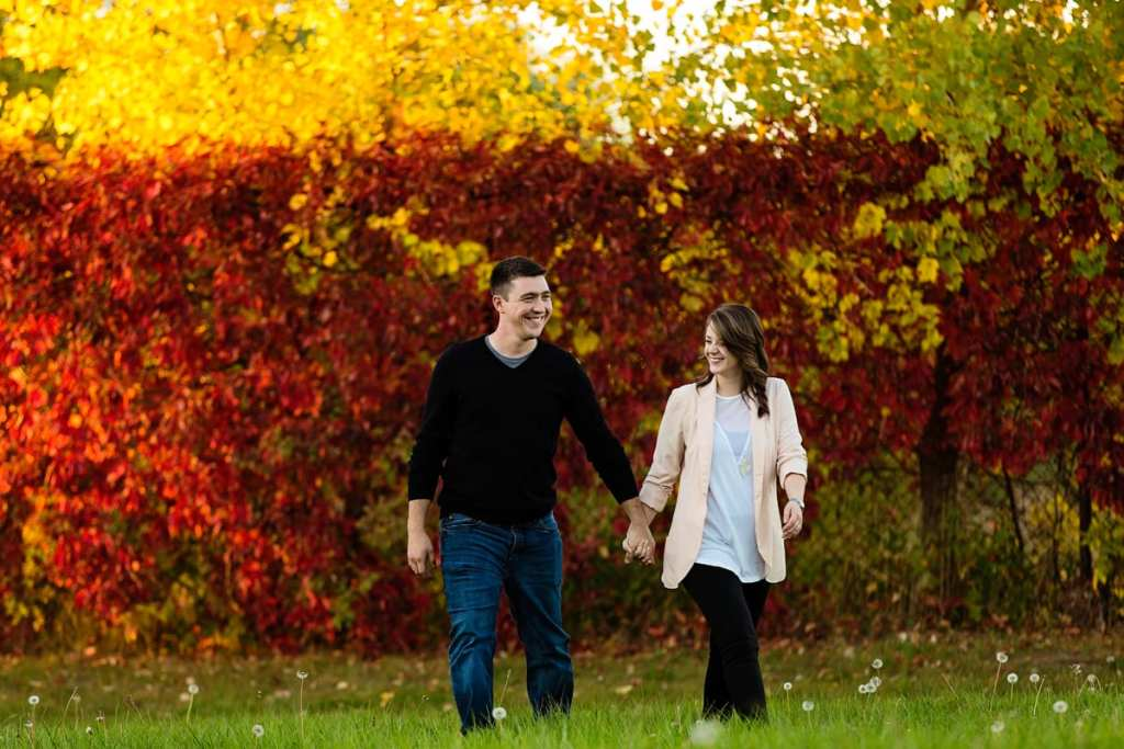 couple holding hands and laughing in front of fall foliage during Autumnal Cornwall engagement session