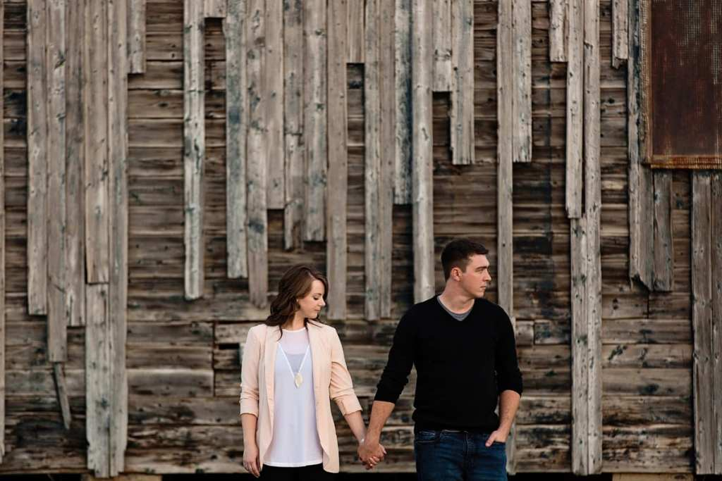 man and fiancee on rustic background in modern fall engagement session