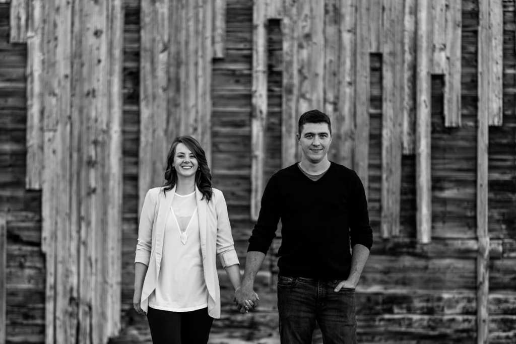 couple holding hands in front of rustic building in fall engagement shoot