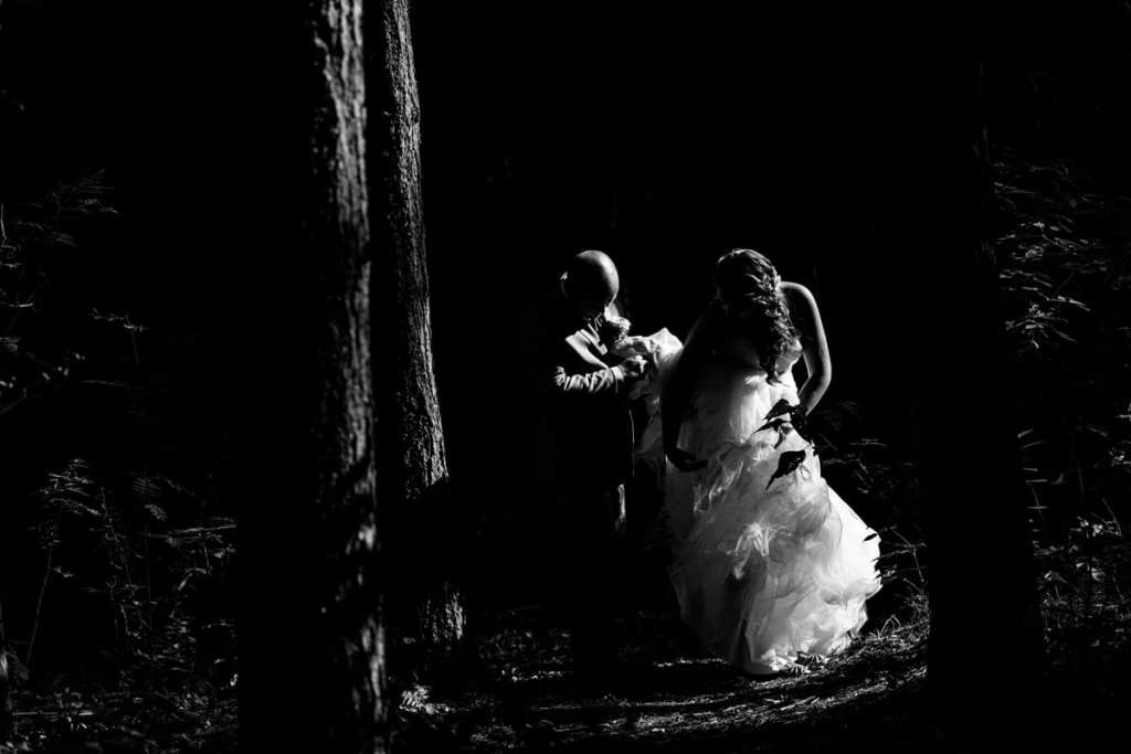 groom helps bride with fit and flare gown in the forest