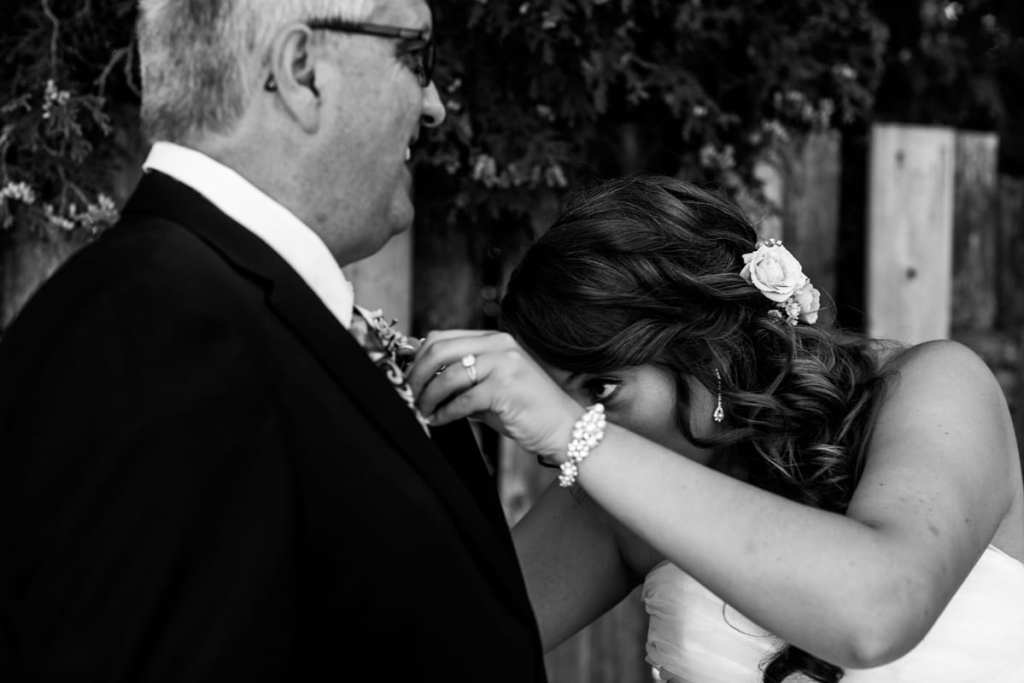 Cornwall bride attaches boutonniere to father's lapel