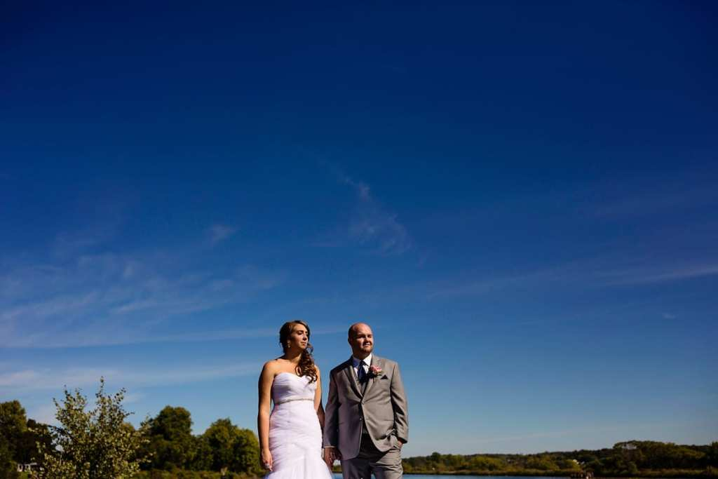 bride and groom look towards sun while holding hands