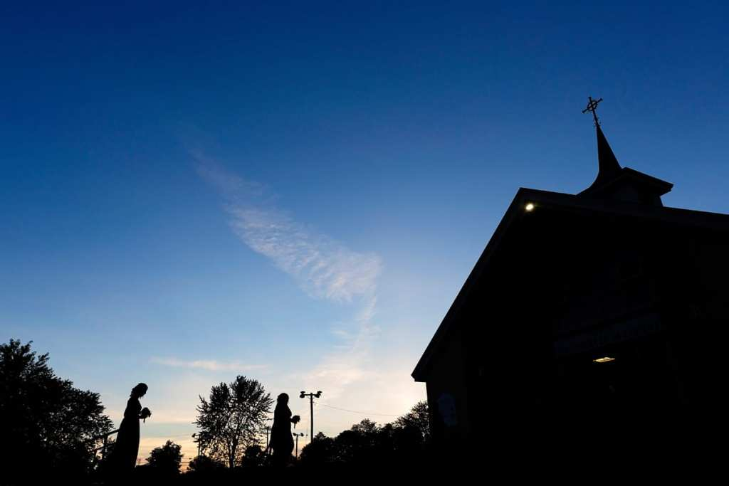 Bridesmaids walk to church at dusk for Cornwall evening wedding