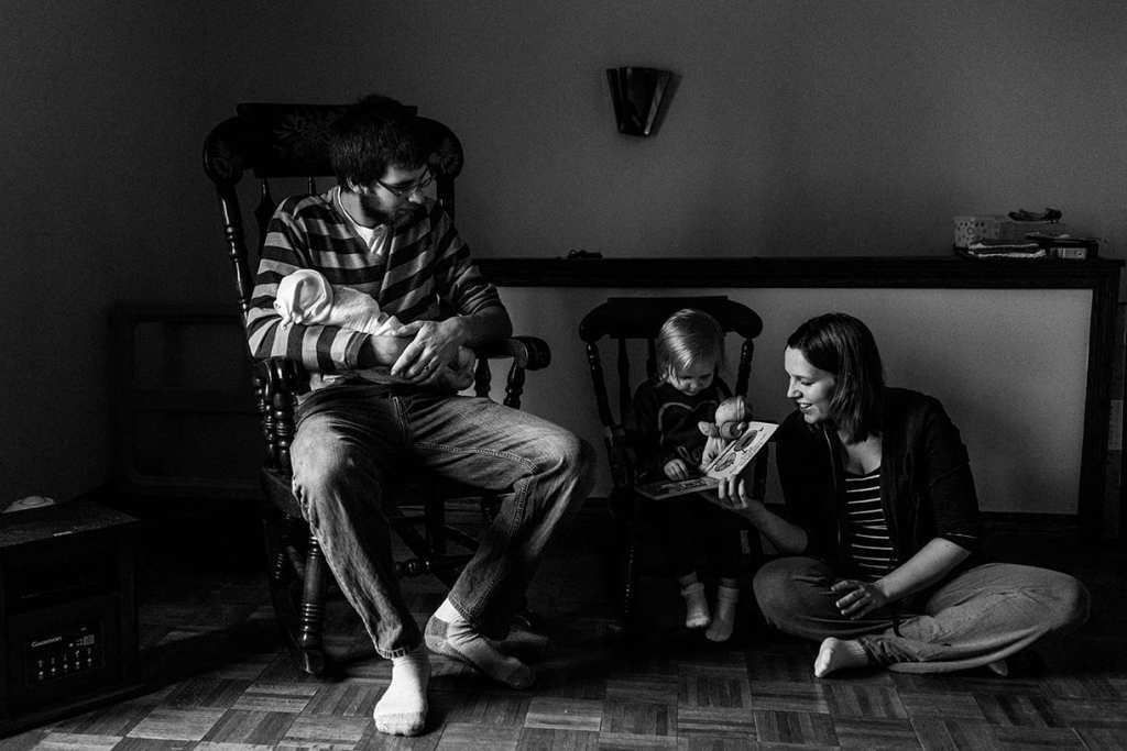 family reading book in rocking chairs during session with Ottawa family photographer