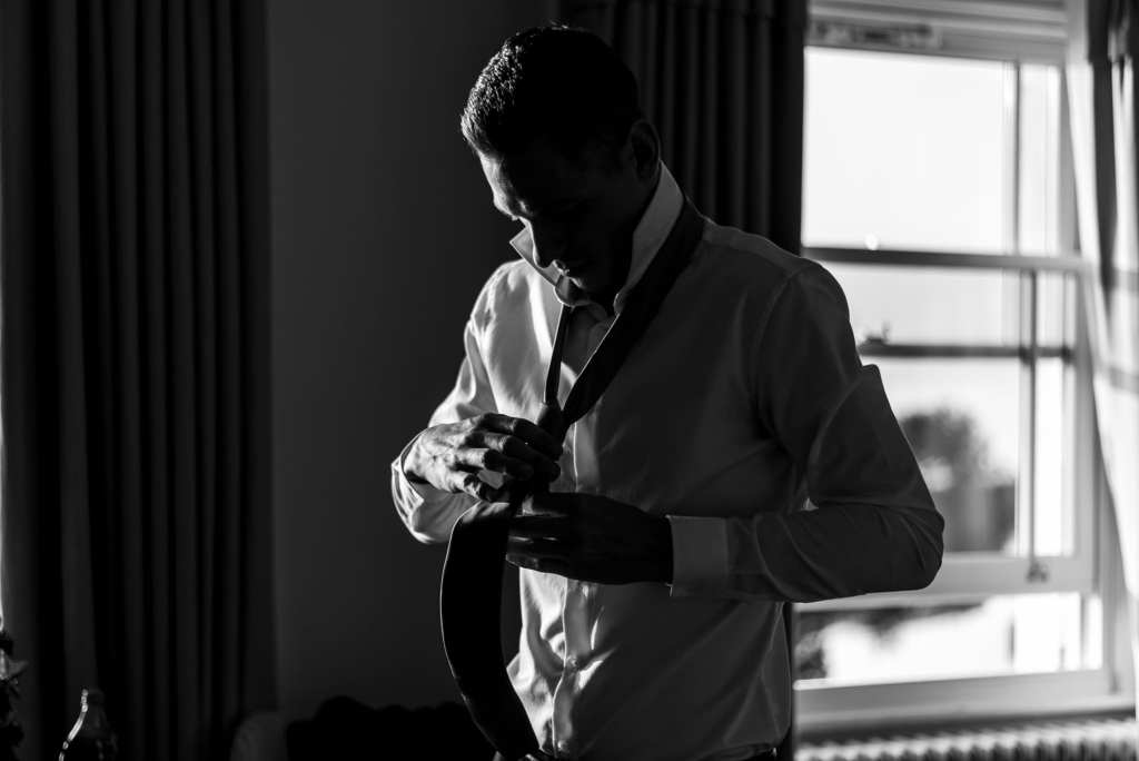 groom holds out tie with tying it during groom prep at Christchurch Habour Hotel & Spa