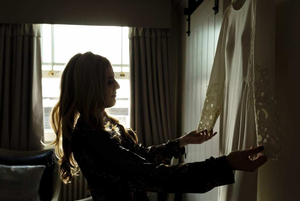 bride holds out sleeves of dress and looks at bespoke wedding gown in backlight from window during bridal prep at Christchurch Habour Hotel & Spa