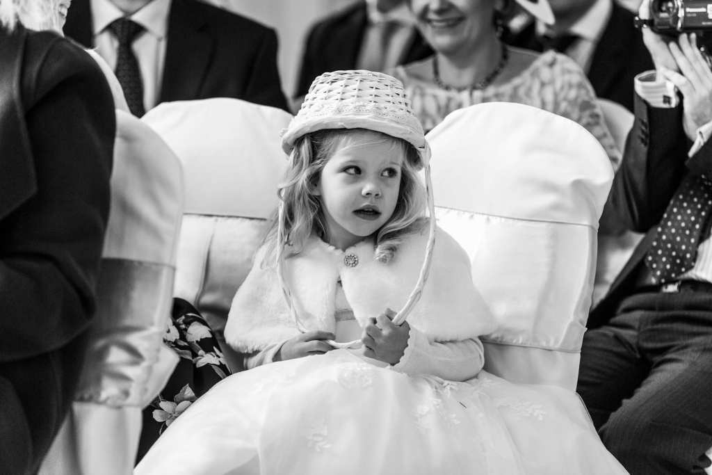 flower girls wears flower basket on her head during chic New Forest wedding ceremony at Highcliffe Castle