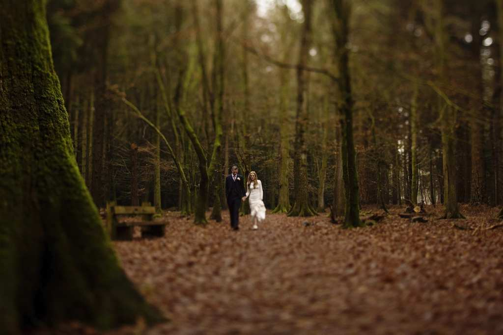 Bride holds dress and groom's hand while walking through the leaves on Rhinefield Ornamental Drive during New Forest wedding portraits