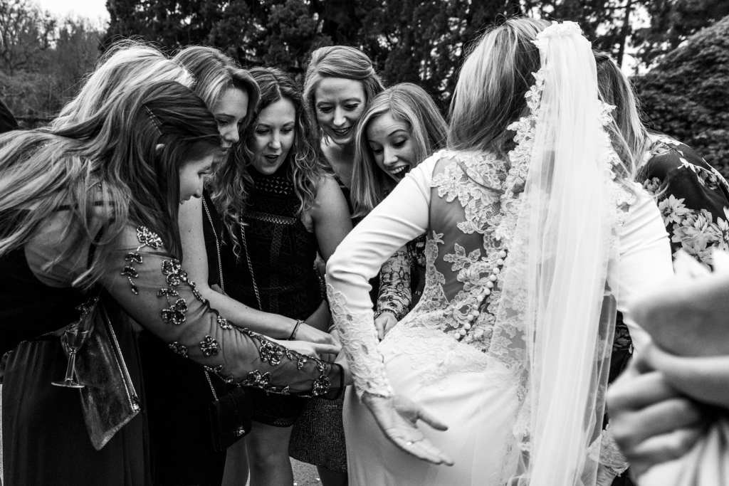 women gather round bride and look surprised while touching her bum during wedding reception at Rhinefield House