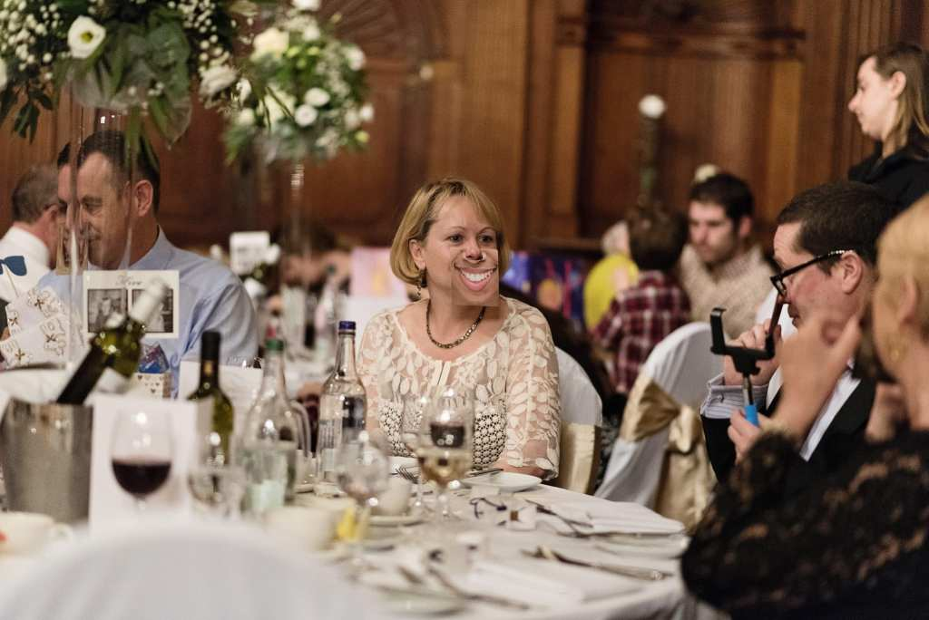 woman in formal dress wears cardboard cutout on her face of big toothy grin during wedding reception at Rhinefield House