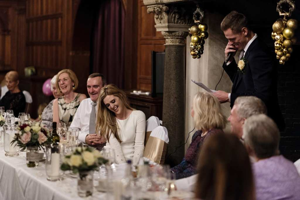 Bride looks down bashfully while groom gives speech during wedding reception at Rhinefield House