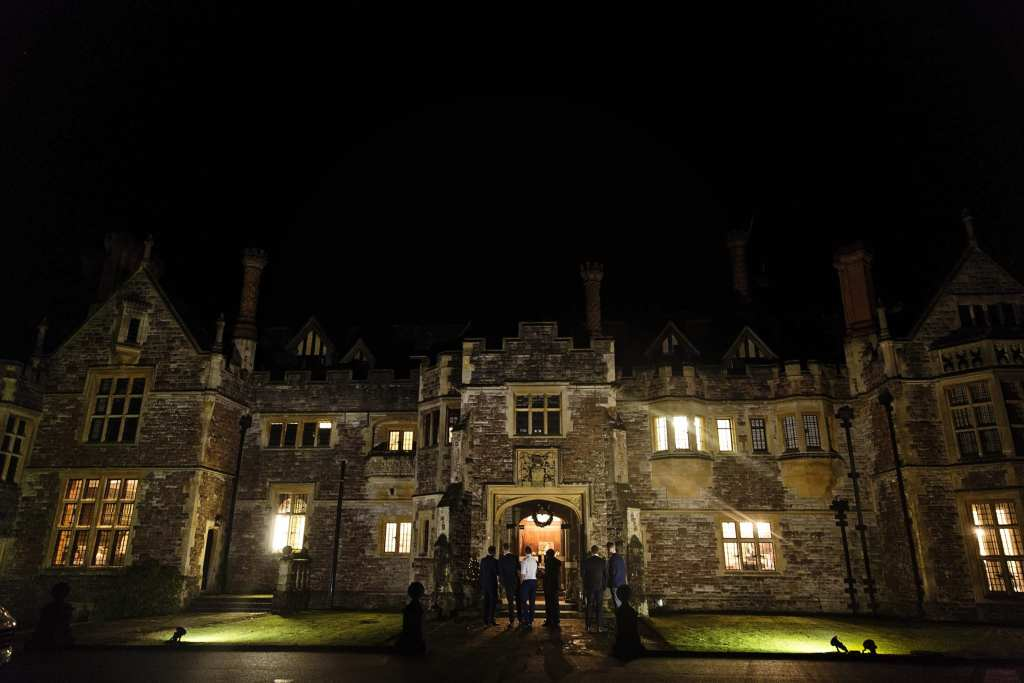 Men stand in front of entrance late into evening during wedding reception at Rhinefield House