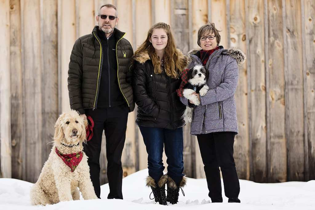 family with large and small dog stand in front of wood shed