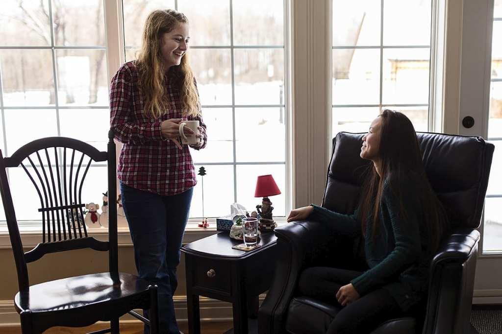 cousins talk near windows while one holds mug