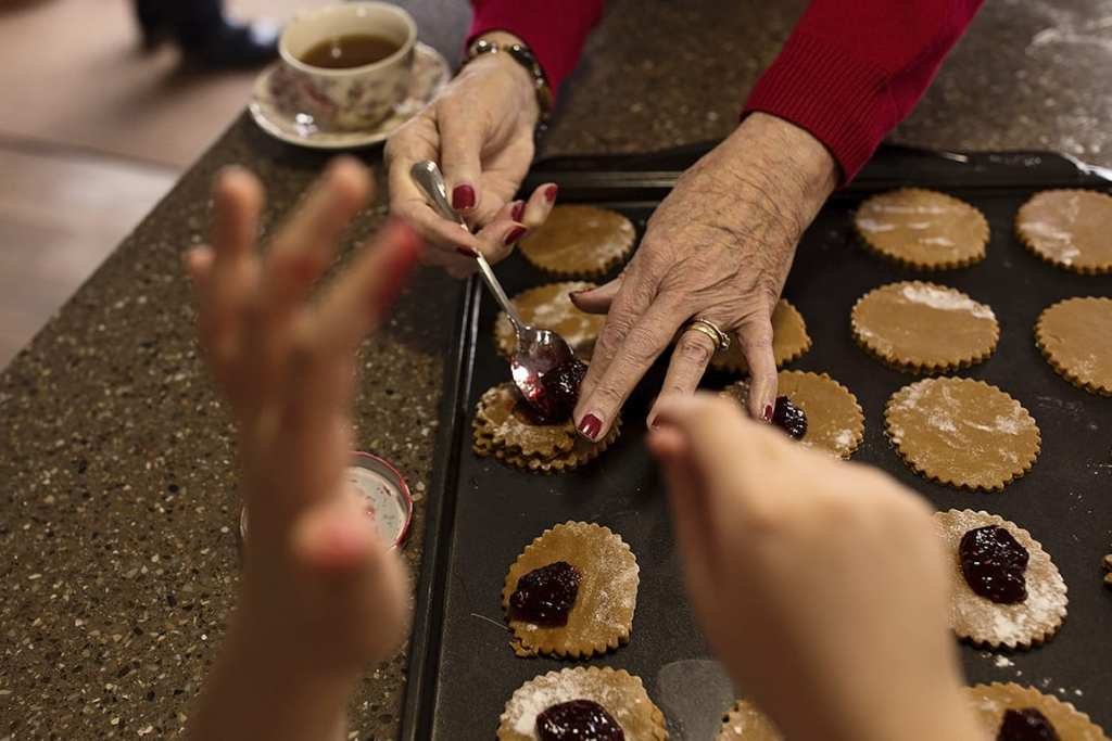grandmother and granddaughter's hands while baking cookies