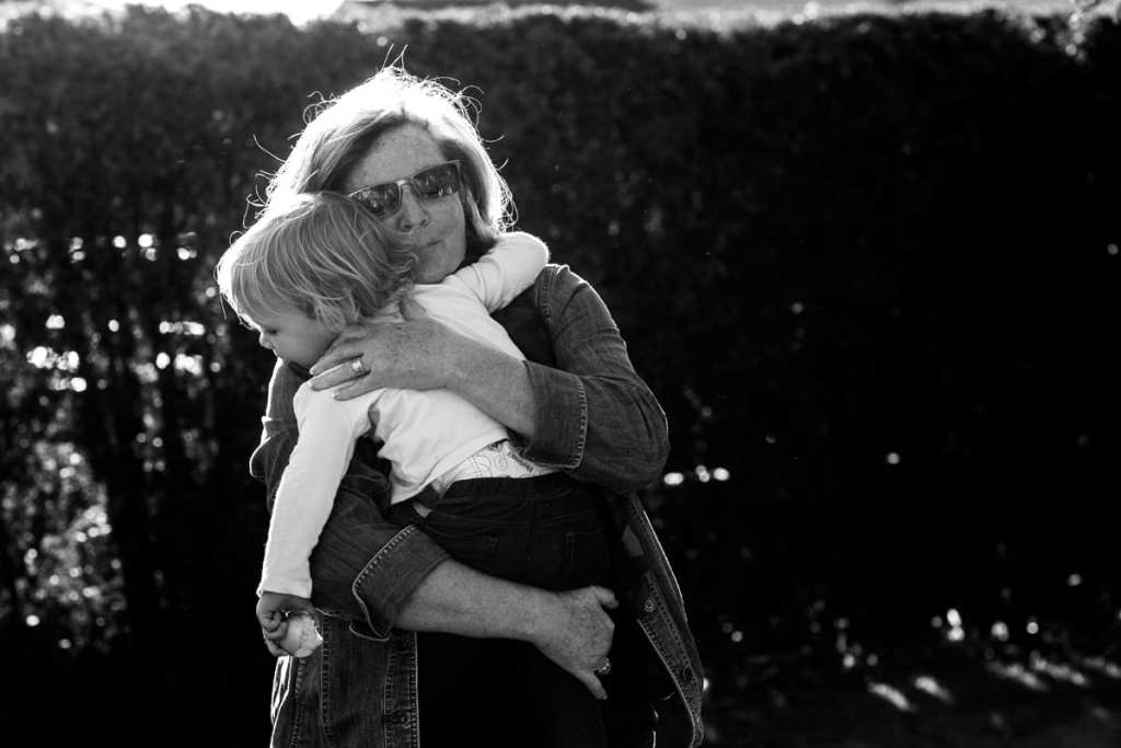 grandmother hugs granddaughter during session with ontario family photographer