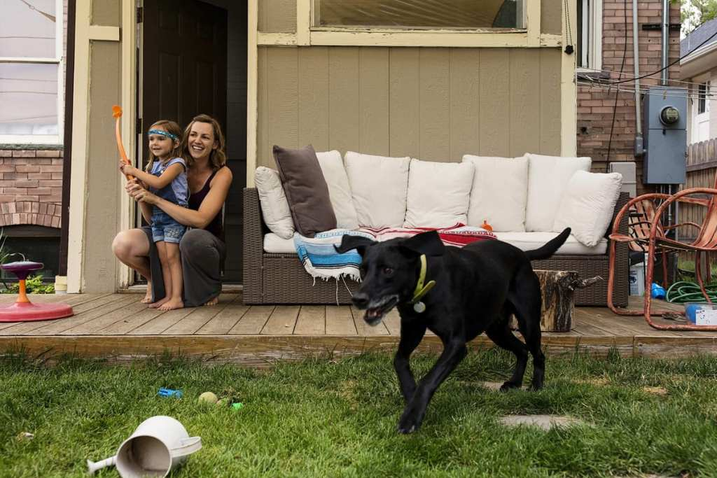 mother holds daughter and helps her throw ball for dog who leaps off deck
