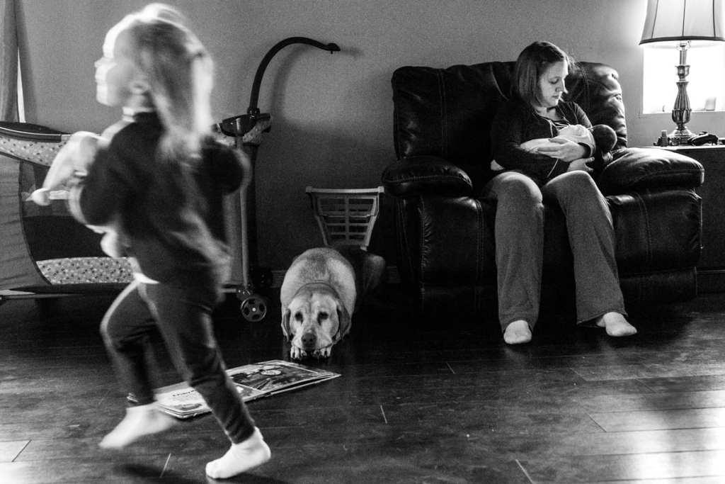 girl runs past breastfeeding mom while dog watches