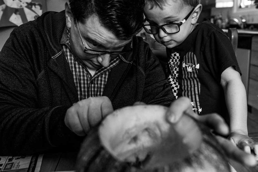 dad and son carve pumpkins