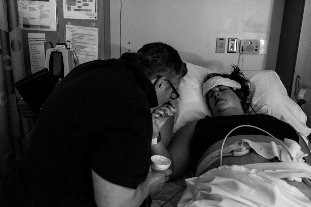 Woman kisses wife's hand during contractions
