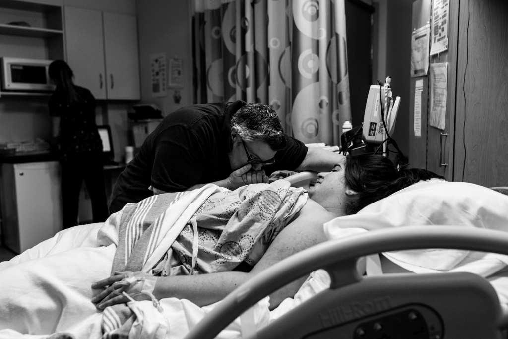 Woman kisses wife's hand between contractions