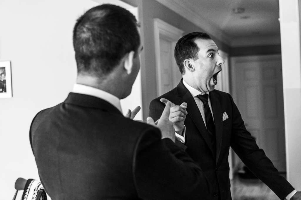 Orange Art Gallery wedding groomsman reacts in surprise and points at friend