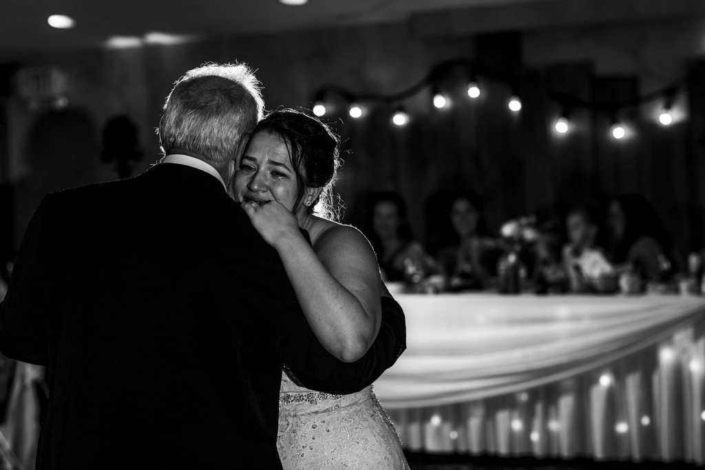 bride cries while dancing with father