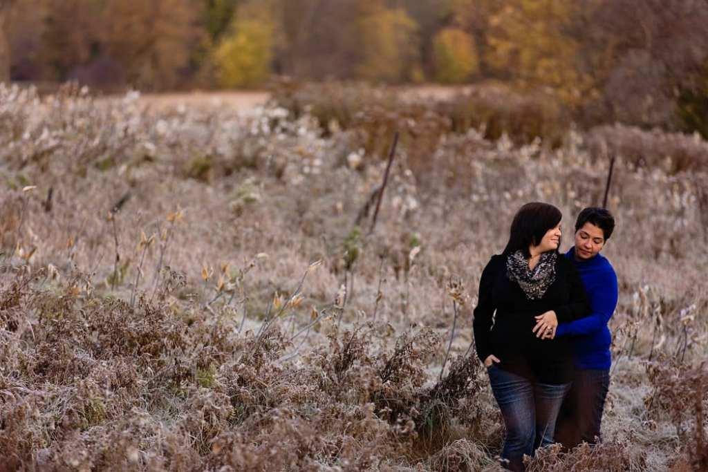 pregnant woman stands with wife in field of milkweed with hand on belly