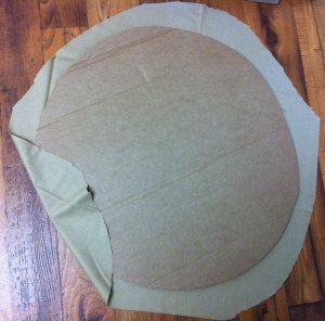 Cut two circles from the tan fabric. They should be a bit larger than the cardboard circles. Glue the fabric to the cardboard, but leave about six inches unglued.