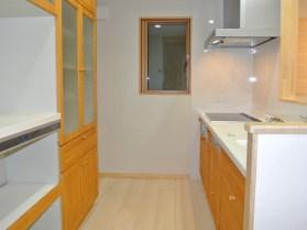 アクセントのきいたシステムキッチンに大容量の食器棚