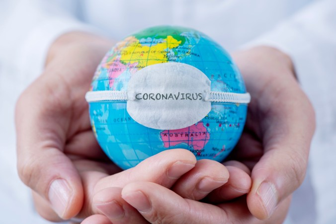 Hands holding a world globe with a mask with the coronavirus written on it