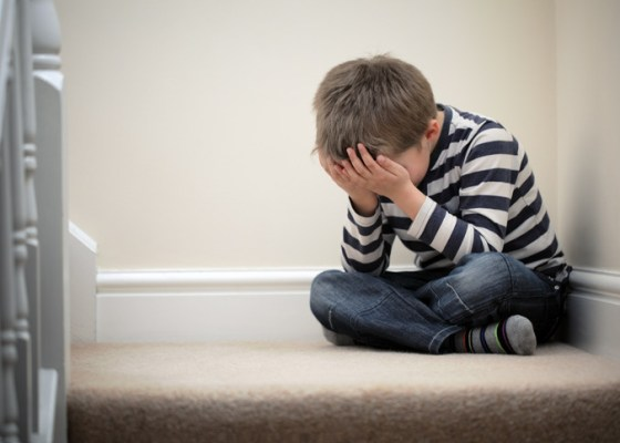 Anxious child sitting on stairs with face in hands