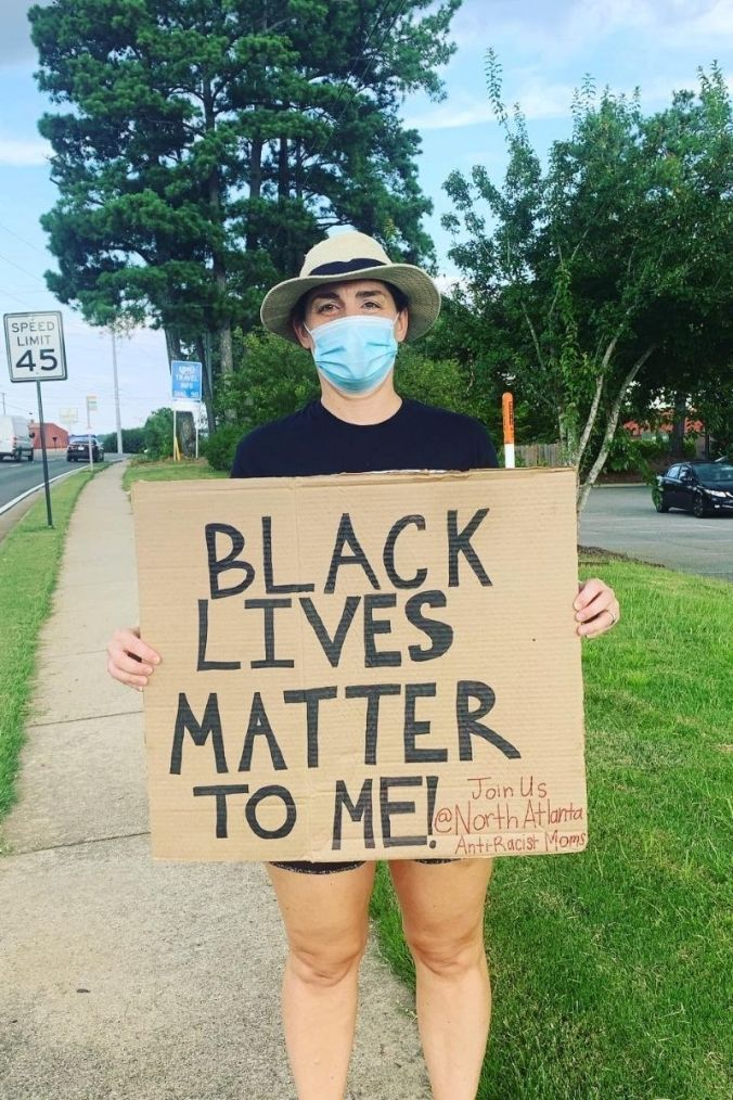 mom holding sign at antiracist moms protest that says Black Lives Matter to me