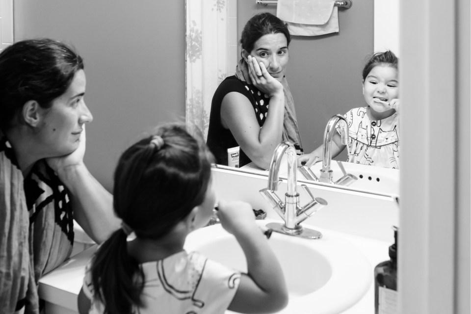 Mom watching daughter brush teeth