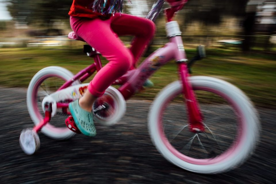 little girl ridding a pink bike