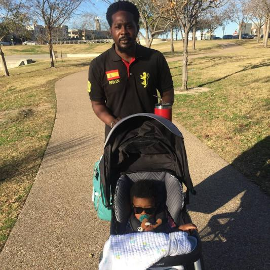 Father walking through a park while pushing his son in a stroller