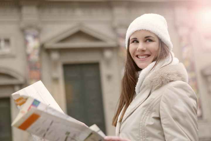 smiling female tourist with paper map on street
