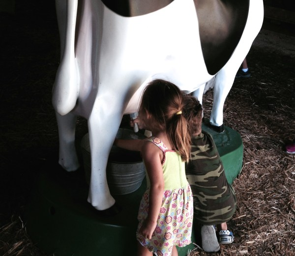Charlie and Maddie practicing milking a cow.