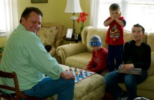 Jeff, Sam, Charlie, and Noah playing checkers I think.