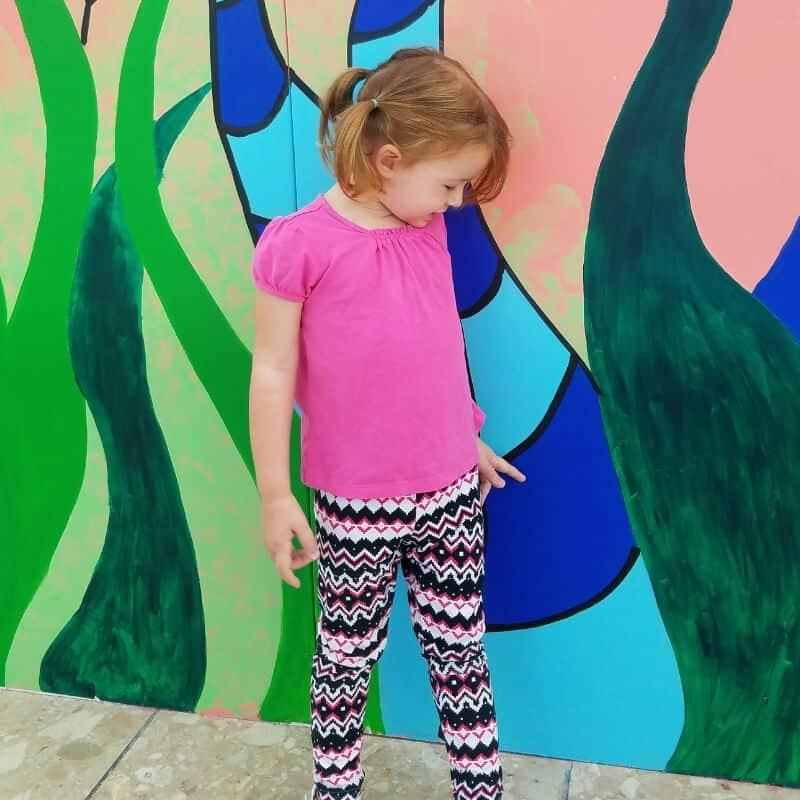 toddler girl by mural