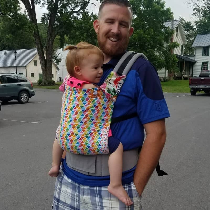 Dad wearing toddler girl in Tula baby carrier
