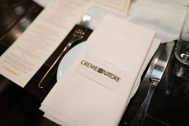all white place setting that reads Creme of Nature