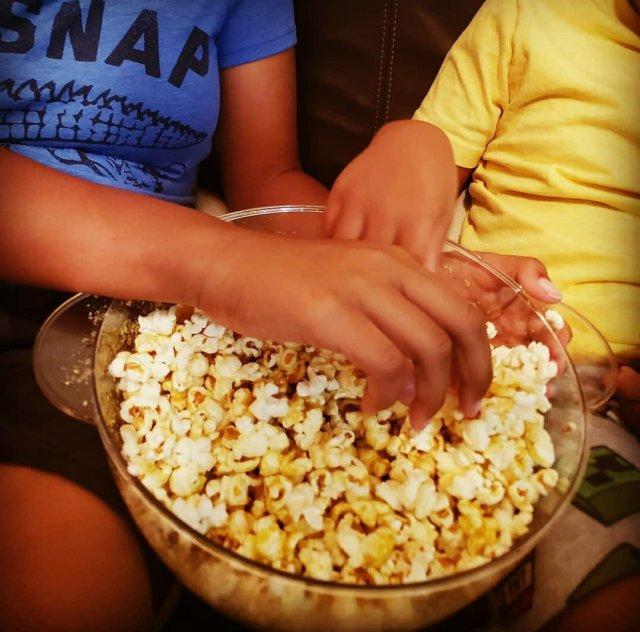 kids hands digging in popcorn