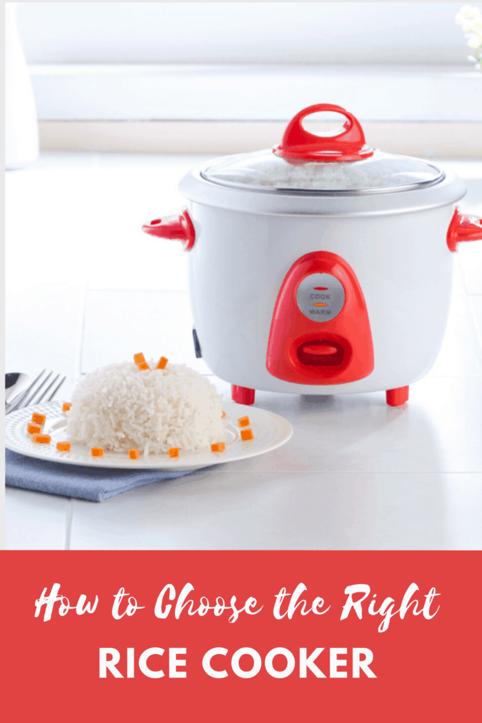 white rice cooker with red accents with plate of rice, garnished next to the rice cooker
