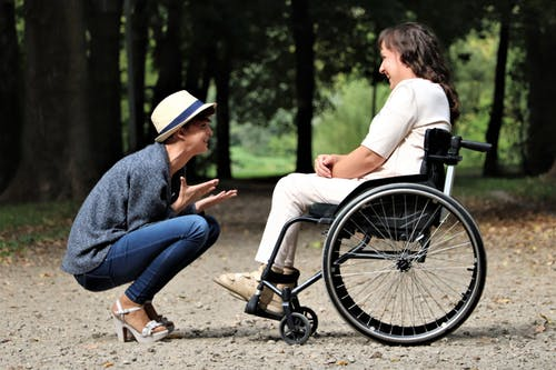 woman sitting in wheelchair with woman bending down to talk to her